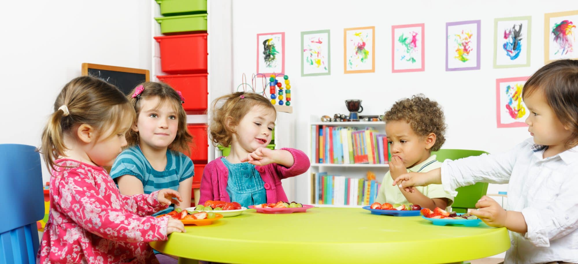 A portrait of group of children having fruit at nursery.Nikon D3X. Converted from RAW.Note to Inspector: artwork done by photographer.