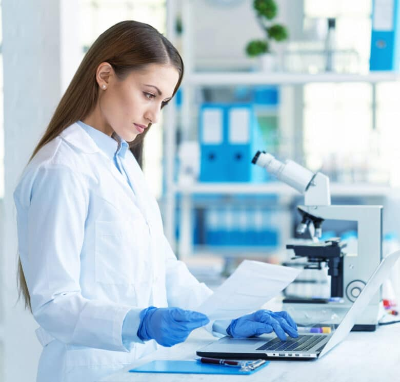 Young female scientist using laptop and microscope in laboratory.